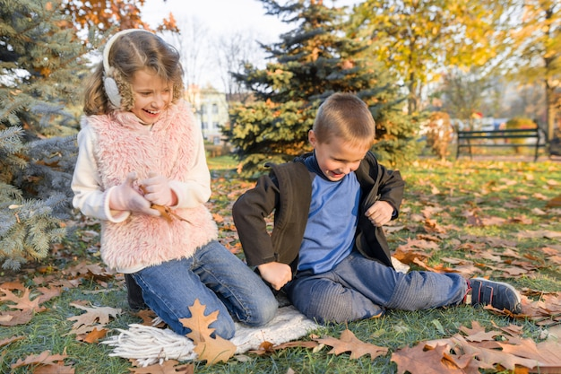 Enfants heureux jouant et assis sur des feuilles jaunes
