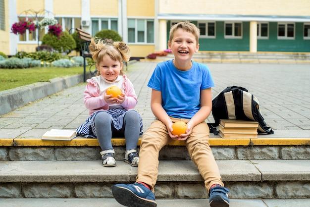 Enfants heureux jouant dans la cour de l'école à l'heure du jour. petit-déjeuner scolaire, fruits et jus. pile de manuels, livres. bonne soeur et frère
