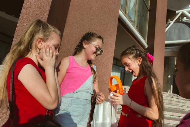 Enfants heureux jouant dans la rue de la ville en journée d'été ensoleillée devant un bâtiment moderne. groupe d'enfants ou d'adolescents heureux s'amusant ensemble. concept d'amitié, enfance, été, vacances.