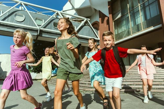 Enfants heureux jouant dans la rue de la ville en journée d'été ensoleillée devant un bâtiment moderne. groupe d'enfants ou d'adolescents heureux s'amusant ensemble