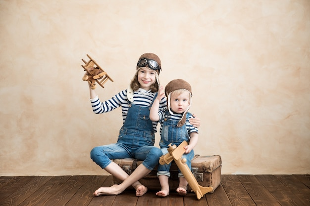 Enfants heureux jouant à la maison. bébé garçon et fille avec avion jouet