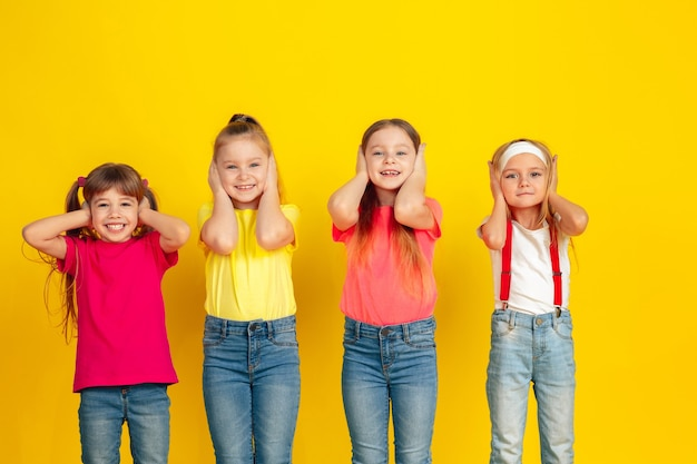 Enfants heureux jouant et s'amusant ensemble sur le mur jaune