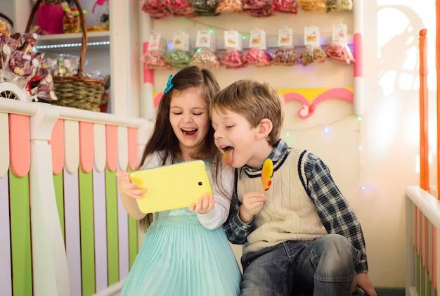 Enfants heureux, jouer à la tablette dans le magasin de bonbons