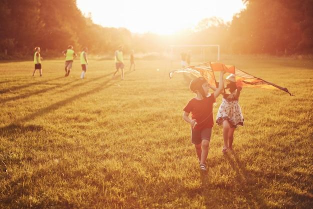 Des enfants heureux lancent un cerf-volant sur le terrain au coucher du soleil. petit garçon et fille en vacances d'été