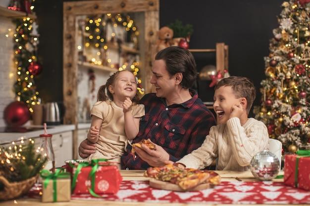 Enfants heureux avec papa mangeant de la pizza dans la cuisine décorée pour noël