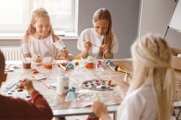 Enfants heureux peignant sur papier avec des peintures colorées à l'école