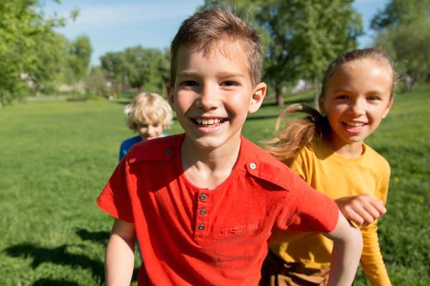 Enfants heureux de plan moyen dans la nature