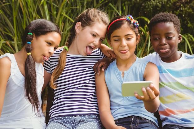Enfants heureux prenant selfie au parc