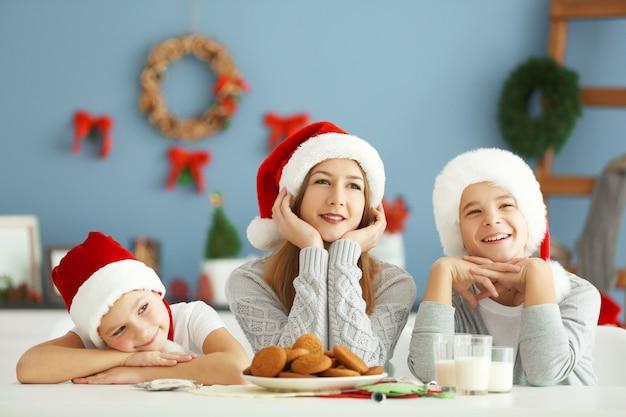 Des enfants heureux prennent un repas dans une salle de noël décorée