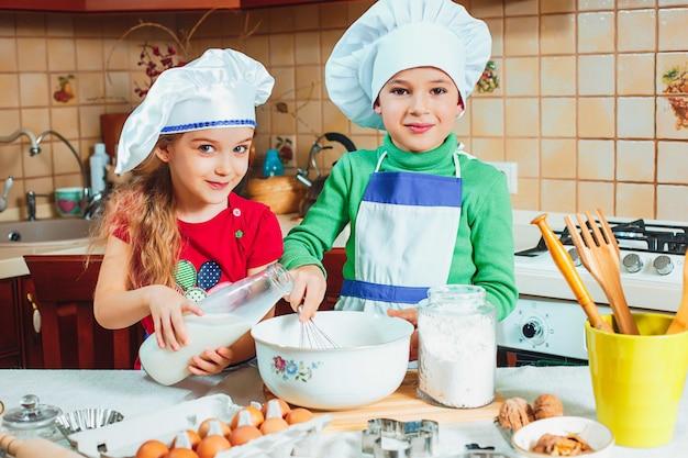 Des enfants heureux préparent la pâte