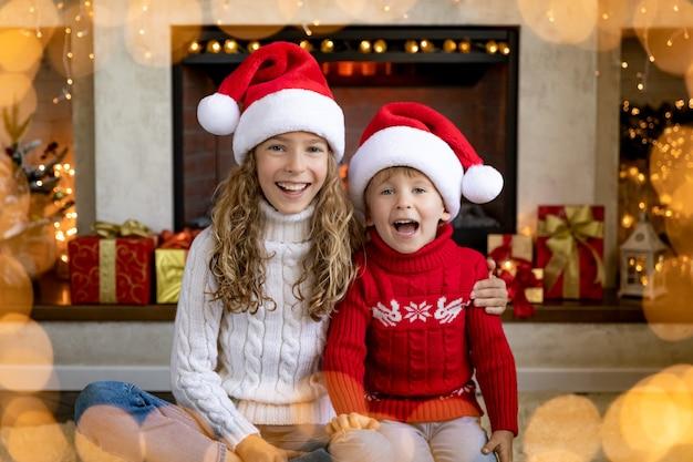 Enfants heureux près de la cheminée à noël. les enfants s'amusent à la maison.