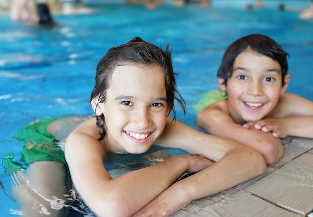Enfants heureux, profitant de la piscine d'été