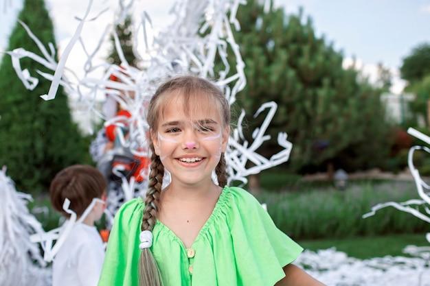 Des enfants heureux profitent d'un spectacle de papier lors d'une fête d'anniversaire en plein air dans le jardin