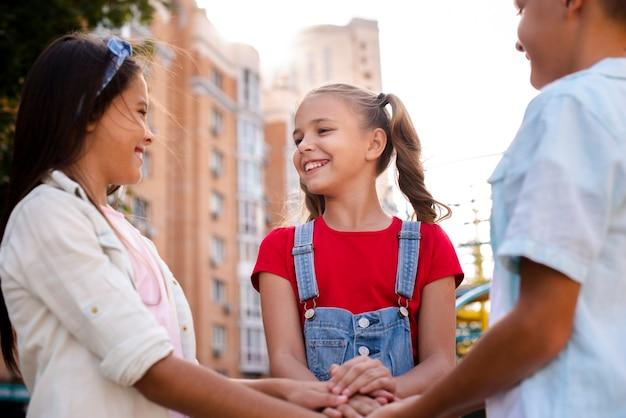 Des enfants heureux qui mettent leurs mains ensemble
