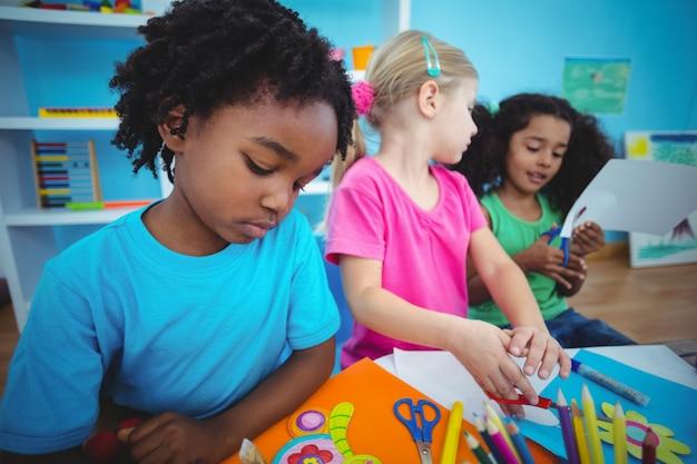 Enfants heureux en utilisant la pâte à modeler ensemble