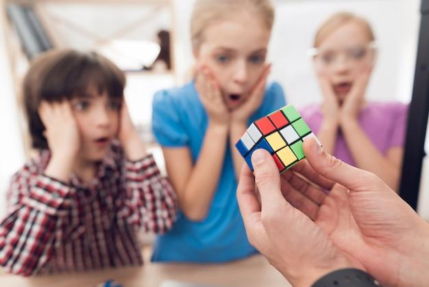 Les enfants impriment différents éléments sur une imprimante 3d avec un enseignant.