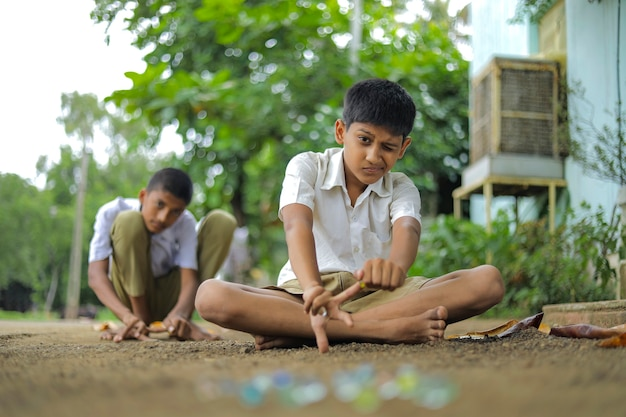 Enfants indiens jouant avec des billes de verre
