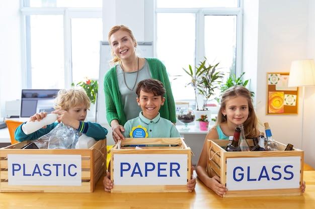 Enfants intelligents. belle enseignante souriante après avoir trié les déchets avec des enfants intelligents de l'école primaire
