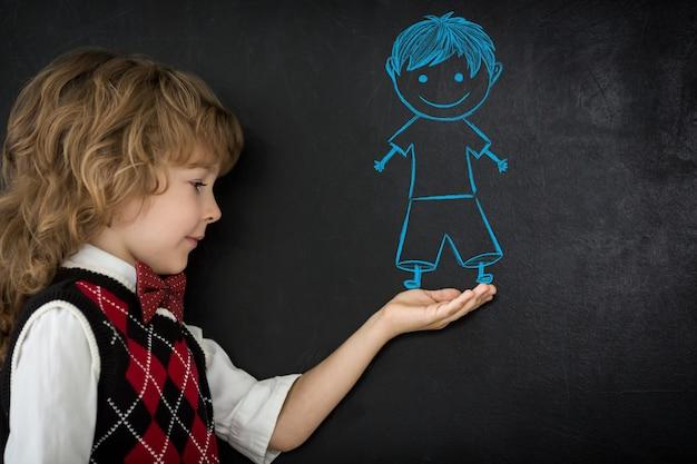 Enfants intelligents en classe. enfants heureux contre le tableau noir. notion d'éducation