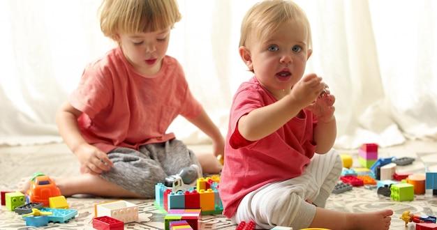 Enfants intelligents dans des vêtements lumineux jouant ensemble érecteur avec enthousiasme assis sur le sol.