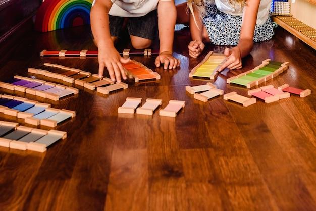 Enfants jouant et apprenant avec des comprimés de couleur montessori