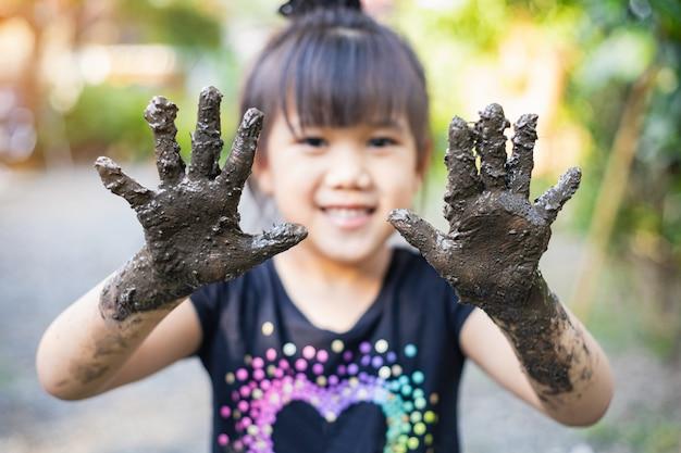 Enfants jouant avec de l'argile boueuse