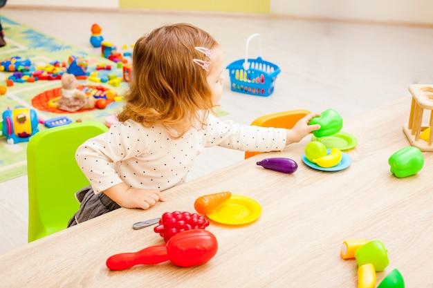 Enfants jouant avec des articles ménagers pour enfants et des fruits artificiels à la maternelle