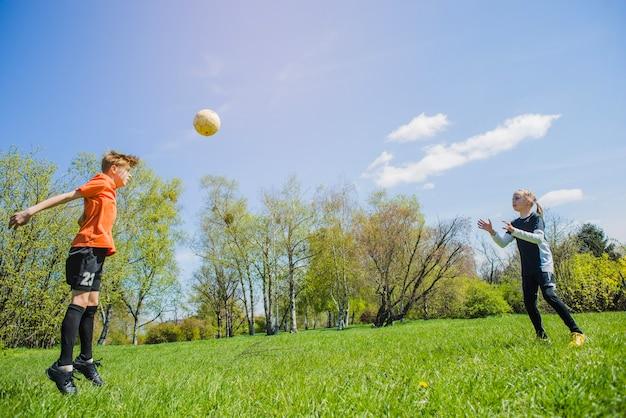 Enfants jouant au football dans le parc