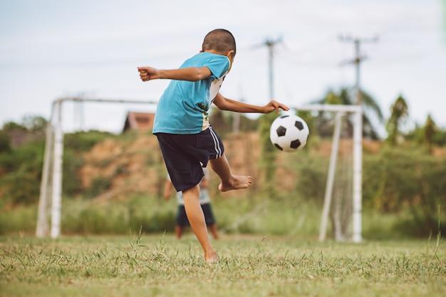 Enfants jouant au football pour faire de l'exercice sur le terrain d'herbe verte