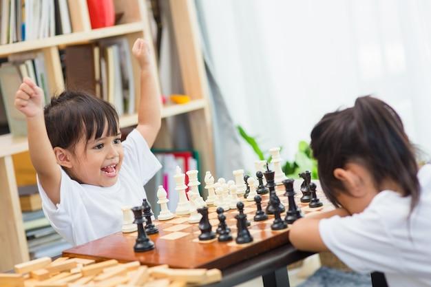 Enfants jouant aux échecs - l'un d'eux vient de capturer un pion et célèbre