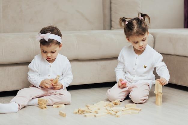 Enfants jouant avec des blocs de bois sur le sol