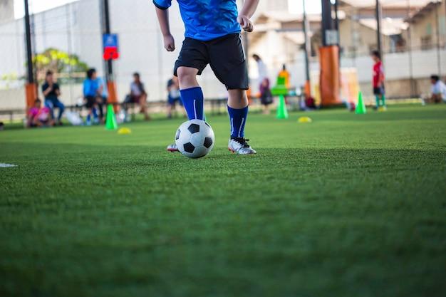 Enfants Jouant Le Cône De Tactique De Ballon De Football De Contrôle Sur Le Terrain D'herbe Avec Pour L'arrière-plan De Formation Formation Des Enfants Au Football Photo Premium