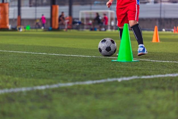 Enfants jouant le cône de tactique de ballon de football de contrôle sur le terrain d'herbe avec pour l'arrière-plan de formation formation des enfants au football