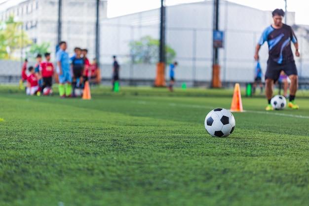 Enfants jouant le cône de tactique de ballon de football de contrôle sur le terrain d'herbe avec pour le fond de formation formation des enfants au football
