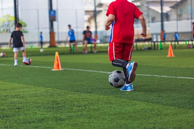 Enfants Jouant Le Cône De Tactique De Ballon De Football De Contrôle Sur Le Terrain D'herbe Avec Pour Le Fond De Formation Formation Des Enfants Au Football Photo Premium