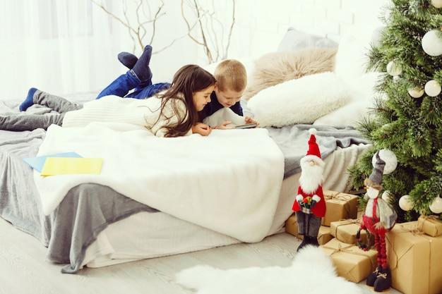 Enfants jouant dans le lit des parents en hiver