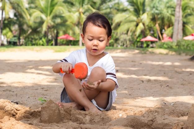 Enfants jouant du sable sur la plage. moment de bonheur en vacances d'été.