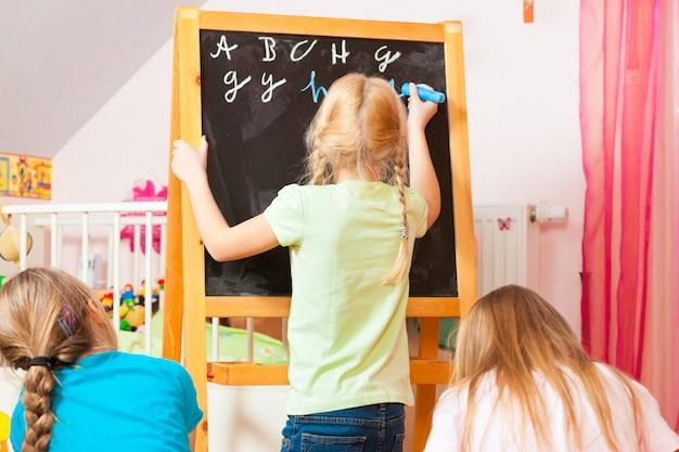 Enfants jouant à l'école à la maison