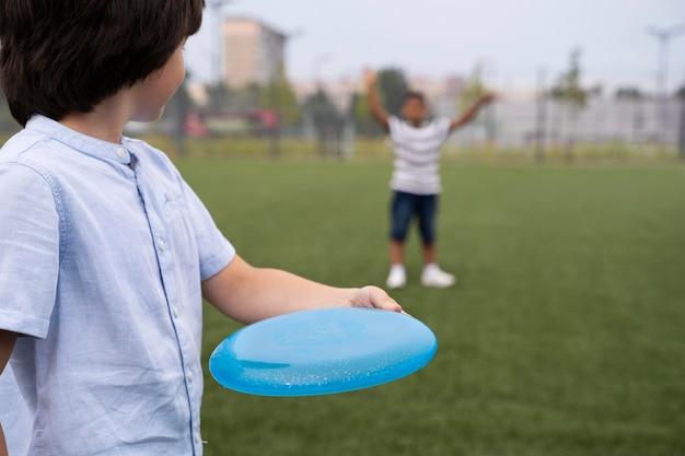 Enfants jouant avec le frisbee se bouchent