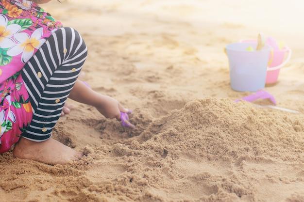 Enfants jouant des jouets sur le sable.