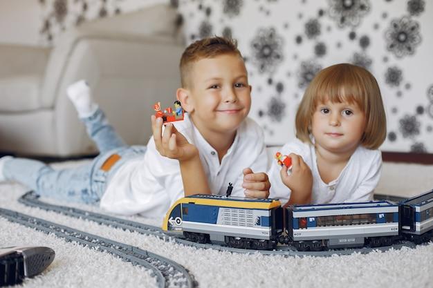Enfants jouant avec lego et train jouet dans une salle de jeux