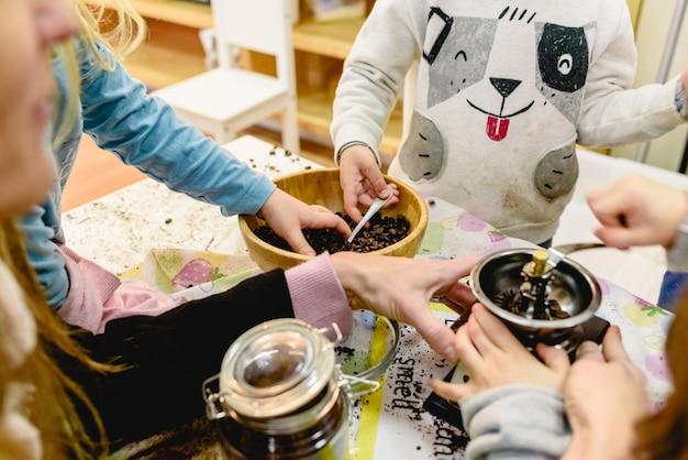 Enfants jouant avec un moulin à café dans une classe de montessori.