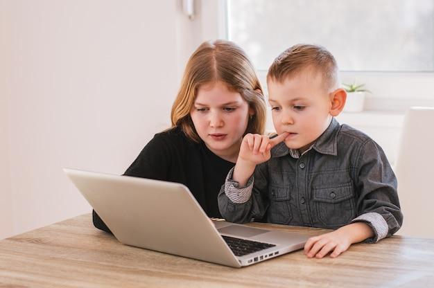 Enfants jouant sur l'ordinateur à la maison