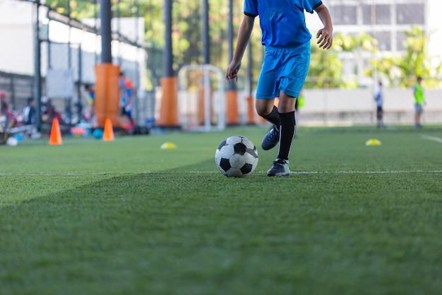 Enfants jouant des tactiques de ballon de football de contrôle sur le terrain en herbe avec pour arrière-plan de formation formation des enfants au football