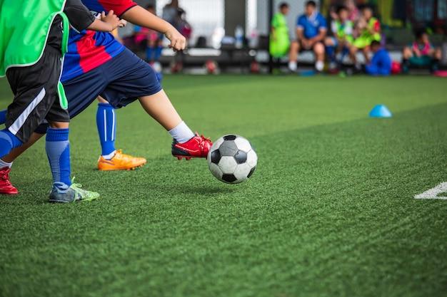 Enfants jouant des tactiques de ballon de football sur terrain en herbe avec pour arrière-plan de formation formation des enfants au football