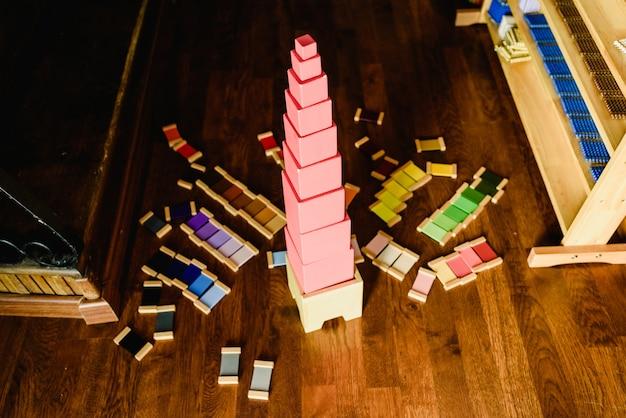 Enfants jouant avec une tour rose dans une classe montessori