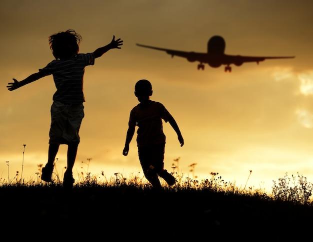 Les enfants jouent contre le soleil sur le coucher du soleil de l'été avec un avion dans l'air