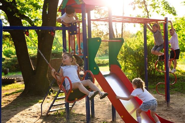 Les enfants jouent à l'extérieur en courant et en s'amusant dans un parc entouré de nature