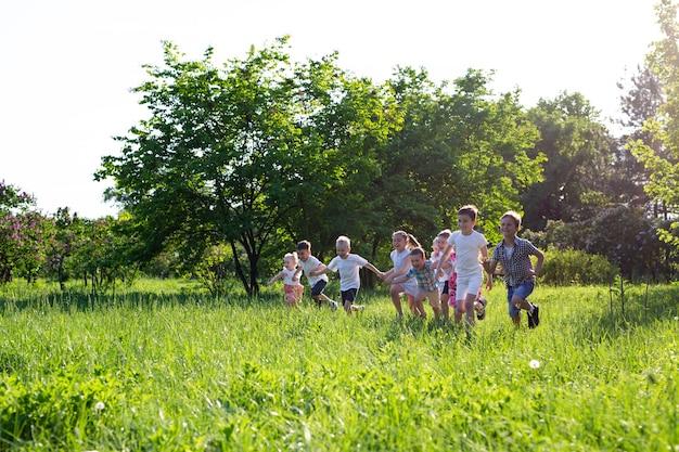 Les enfants jouent à l'extérieur en courant et en s'amusant sur un terrain en herbe