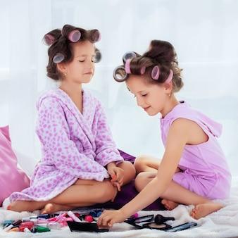Les enfants jouent avec des produits cosmétiques. carré.